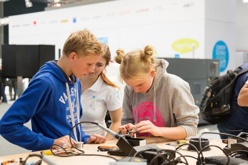 Jugendliche Besucher arbeiten konzentriert am Bau eines Formel-1-Modellrennwagens. Er ist das Highlight für jeden jugendlichen METAV-Besucher.