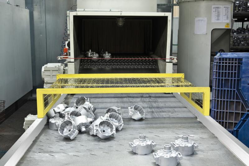 Aluminium Druckguss-Teile am Auslauf einer AGTOS Drahtgurt-Strahlanlage