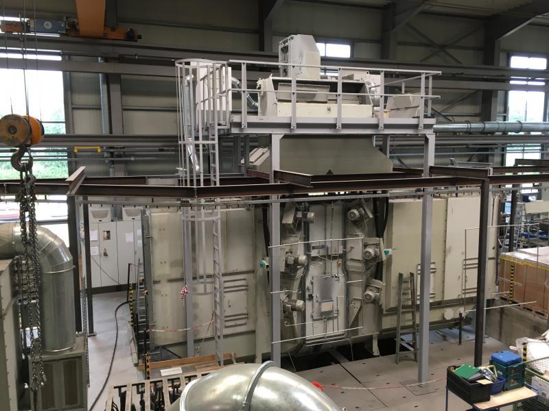 Testzentrum DHT für Aluminium: AGTOS Durchlaufhängebahn-Strahlanlage für die Bearbeitung von Werkstücken aus Aluminium.