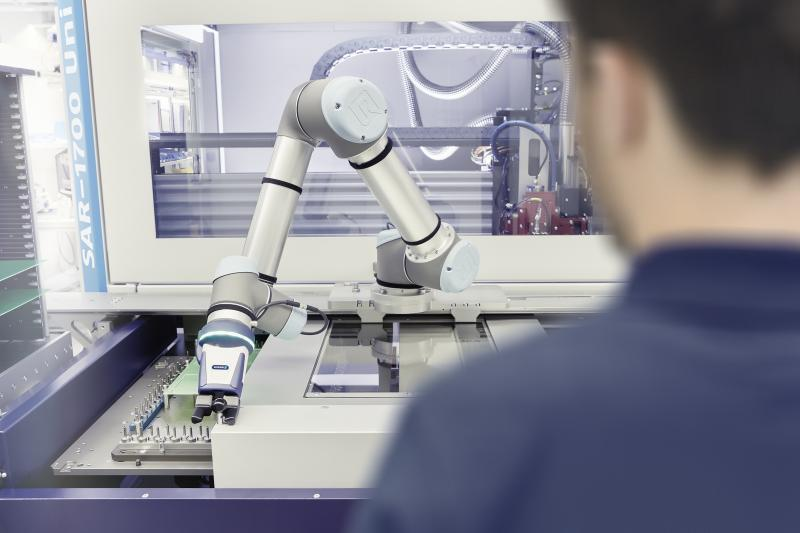 Teamwork in the electronics industry: With this depanelling machine, a robot arm equipped with SCHUNK Co-act EGP-C gripper supports the operator while loading. Photo: SCHUNK