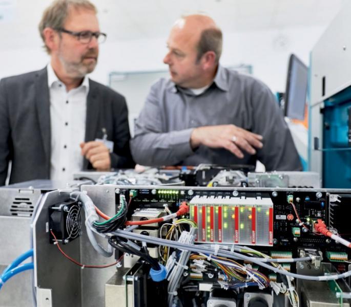 Martin Dimpfl (rechts), Leiter Electronic Engineering im Mühlbauer Unternehmensbereich Automation, demonstriert Martin Bauer, Beckhoff Niederlassung Regensburg, wie die hochkompakte Bauweise über ausziehbare, ebenfalls mit EJ-Modulen (Bildvordergrund) ausgestattete Maschinenmodule realisiert wurde.