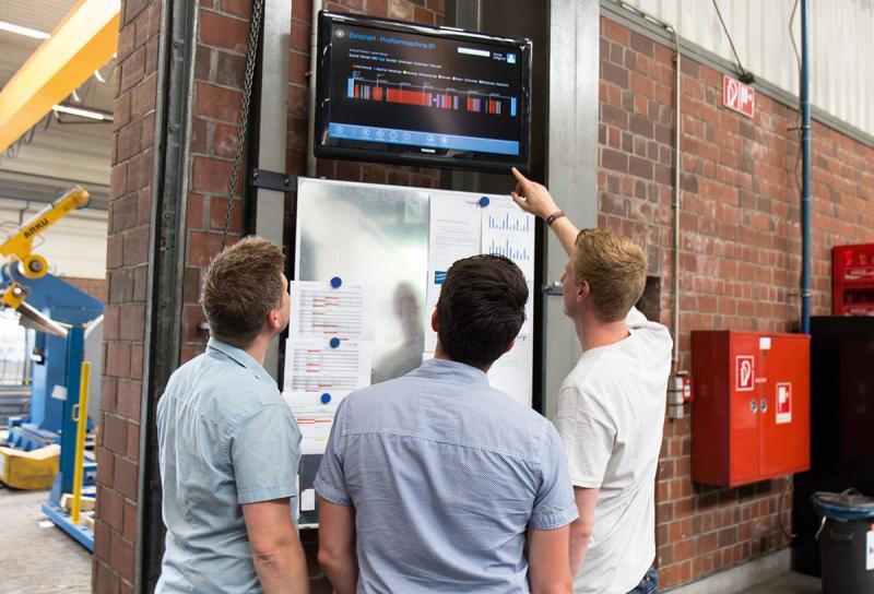 Transparenz in der Halle – Den Produktionsmitarbeitern bei Tillmann gibt ein großer TV-Monitor in der Fertigungshalle live und transparent über alle Produktionsdaten Auskunft.