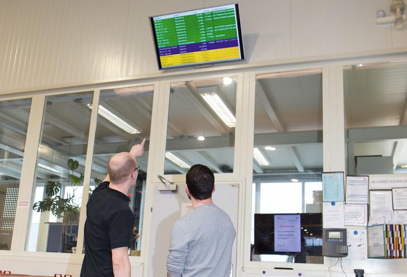 """Groß visualisiert – """"Was wir auswerten, zeigen wir auch her."""" Sämtliche Informationen, die durch das MES erhoben werden, werden in der Fertigung auf großen TVs visualisiert. Diese Transparenz hat sowohl die Motivation der Mitarbeiter als auch den KVP deutlich gesteigert."""