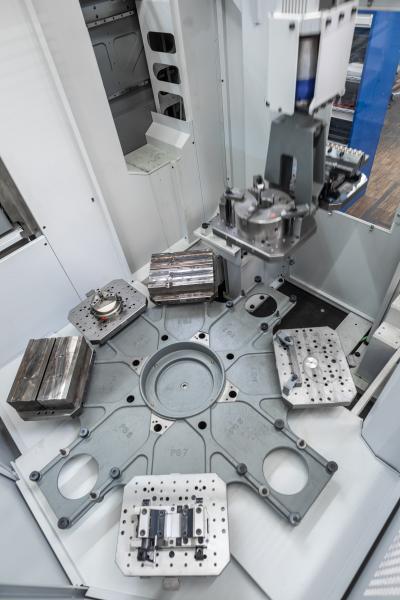 Draufsicht auf den 8-fachen Speicher des 11-fach-Palettenwechslers PW 150 mit acht Paletten im Speicher, zwei Paletten im Wechsler (oben rechts) und einer Palette in der Maschine