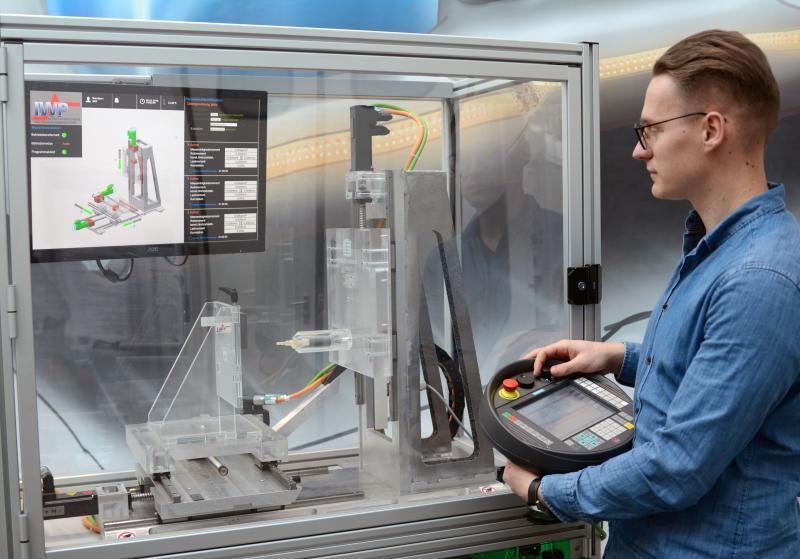 Chris Schöberlein, wissenschaftlicher Mitarbeiter der Professur Werkzeugmaschinen und Umformtechnik, testet den gläsernen Maschinendemonstrator, der den Besuchern auf der Intec-Fachmesse in Leipzig Forschungsergebnisse für die Produktion von morgen näher bringen soll.