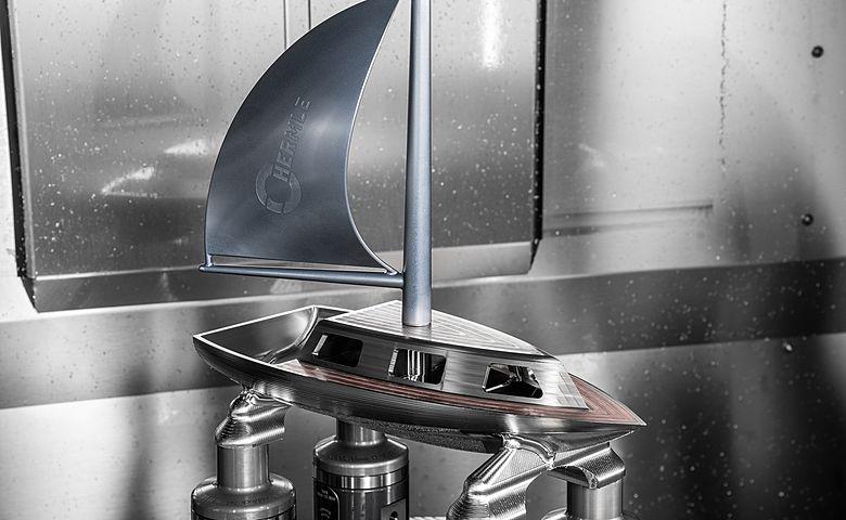Segelboot im Arbeitsraum der Hermle C 400 mit angebautem Segel, die Dach- und Deckfläche aus Kupfer wurden schon freigefräst ebenso die Kajütenfenster in den generativ hergestellten Hohlraum. Das Segel aus Aluminium wurde eloxiert.