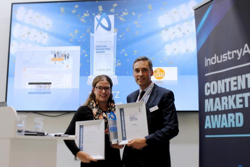 Frank Nolden, Geschäftsführer der IndustryArena GmbH, überreicht Ann-Christin Theyßen von ifm den Award, die Siegerurkunde und den Gutschein für ein Marketing Budget in Höhe von 10.000 Euro