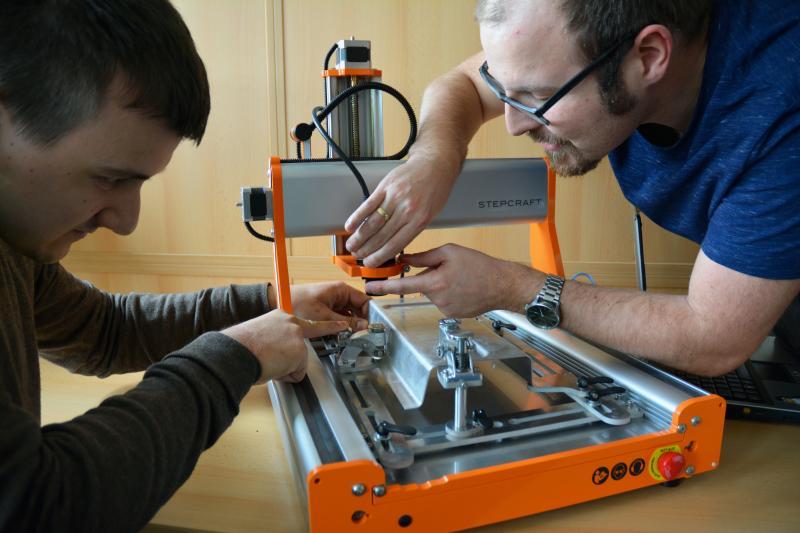 Die Wissenschaftler Nermin Redžić und Felix Pfeiffer bauen ihren Messedemonstrator zur effizienten Teilepositionierung beim 3D-Wasserstrahlschneiden auf.