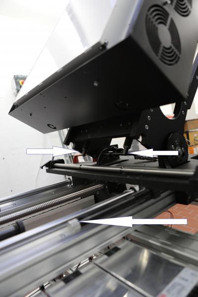 Vorschub-Ölbremse von ACE mit Zahnstangenantrieb senkt die Negativplatte (Pfeil unten) und oben die Vorrichtung zum Hochklappen des Vergrößerers mit ACE Kleinstoßdämpfern und Bolzenvorlagerung für Aufprallwinkel bis zu 25 Grad