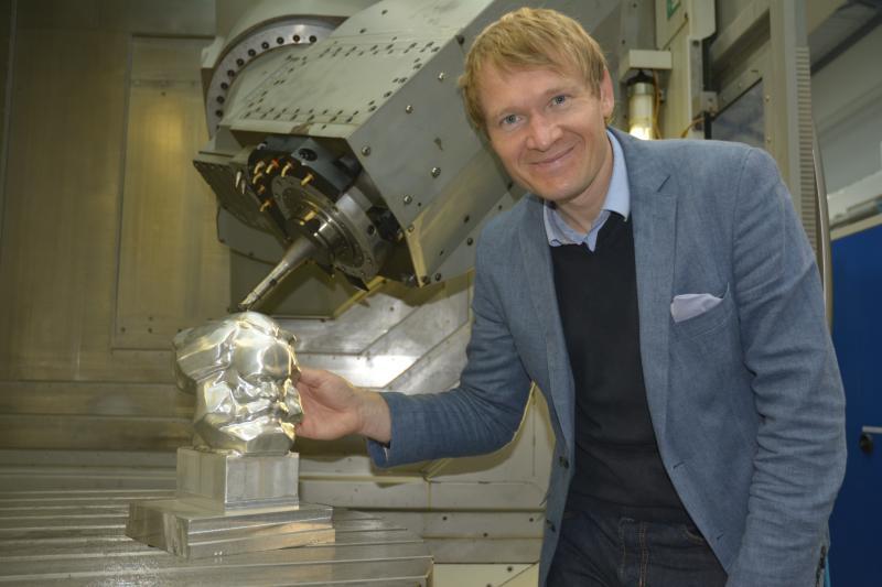 Dr. Philipp Klimant, geschäftsführender Oberingenieur der Professur Produktionssysteme und -prozesse der TU Chemnitz, präsentiert ein Modell des Marx-Kopfes, das aus einem Aluminiumblock gefräst wurde und im Rahmen der Ausstellung zum 50-jährigen Jubiläum der Monumentalskulptur in Chemnitz gezeigt wird.