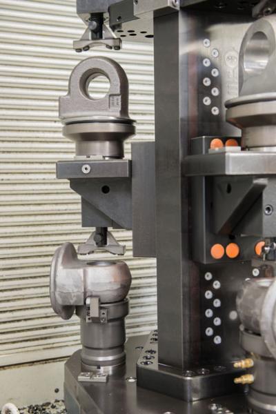 Von oben werden die unterschiedlichen Werkstücke mit einem Druckstück hydraulisch fixiert.