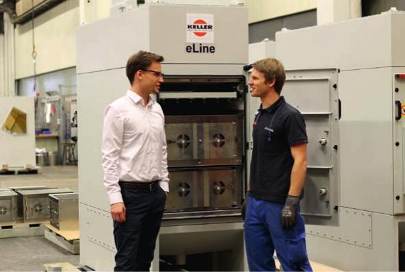Keller-Projektingenieur Thomas Nägele (links) erläutert das Abscheideprinzip des eLine, welches darauf beruht, dass sich positiv geladene Teilchen und ebenso geladene Platten gegenseitig abstoßen.