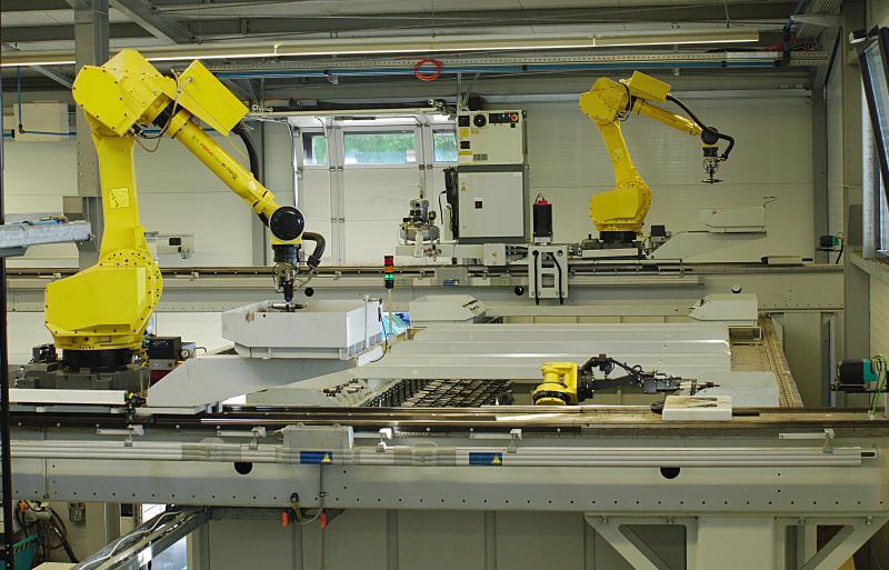Ein Portal-Roboter oberhalb der BAZ am MLS transportiert die Werkzeuge vom zentralen Werkzeugspeicher zu den einzelnen Maschinen. Ein zentraler Speicher, zwei Produktionsstränge, drei Roboter: Ein Roboter im CTS von Fastems (Mitte) sorgt für den Werkzeugtransfer zu den beiden Gantry-Robotern. Im Vordergrund der Roboter, der die Maschinen am MLS versorgt. Im Hintergrund ein weiterer Roboter, der für den Werkzeugtransfer zu fünf weiteren BAZ zuständig ist.